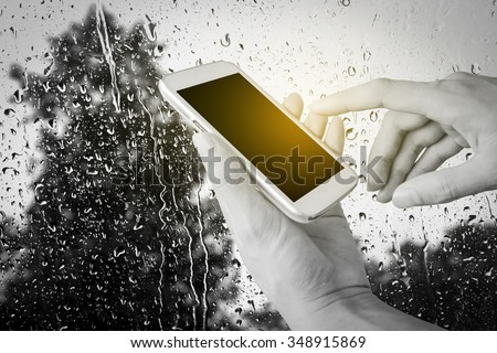 hand of man using mobile phone with blur drop on mirror with tree background - stock photo