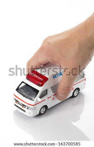 Hand of man with a Ambulance miniature car - stock photo