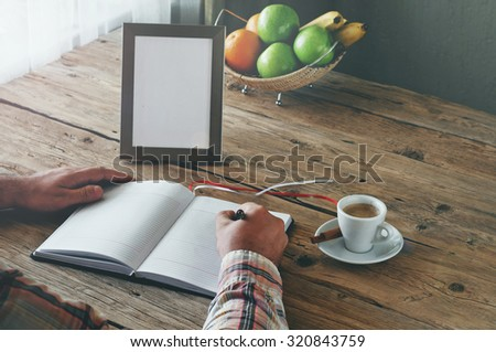 Hand of man writing in a blank notebook on the wooden table. Next on the table is cup of coffee and an empty photo frame. Top view. Copy space. Free space for text - stock photo