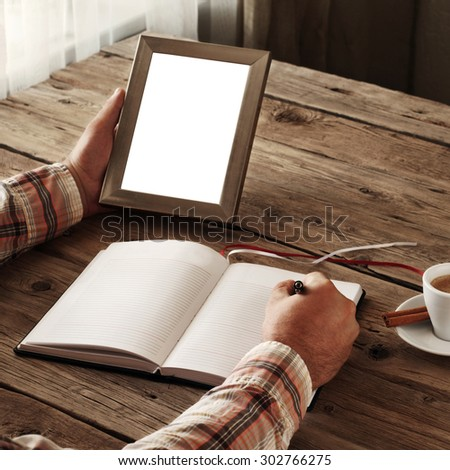 Hand of man writing something in a blank notebook. Other hand man holding an empty picture frame on wooden table. The concept of the memory of something. Top view. Square frame. Free space for text - stock photo