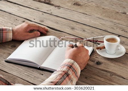 Hand of man writing something in blank notebook on wooden table. Next to the table is a cup of espresso coffee with cinnamon sticks. Closeup. Top view. Copy space. Free space for text - stock photo