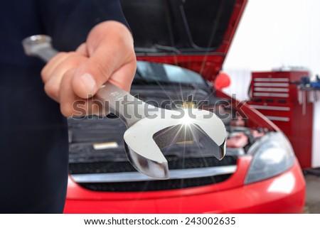 Hand of mechanic with wrench. Car repair garage. - stock photo
