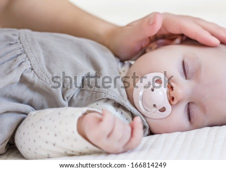 Hand of mother caressing her cute baby girl with pacifier sleeping over white bedcover - stock photo