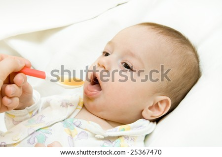 Hand of mother feeds the baby lying on a white bed-sheet. - stock photo