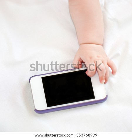 Hand of newborn baby reaches for the mobile phone