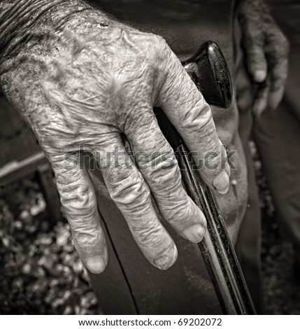 Hand of old man with arthritis supported with walking stick in black and white - stock photo