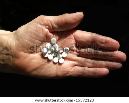 Hand of old women with white tablets - stock photo
