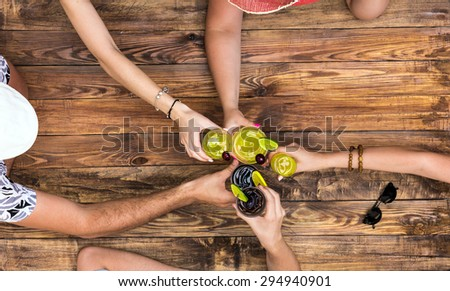 Hand of people cheers with alcohol cocktails at natural handcrafted wooden desk with brown sharp texture casual summer vacation style dress hats - stock photo