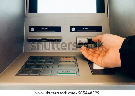 Hand of person using an ATM cash machine.