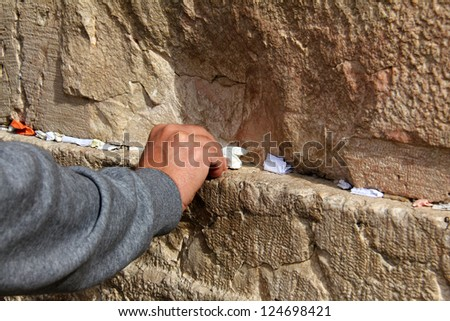 Hand of praying man on the Western Wall  in Jerusalem - stock photo