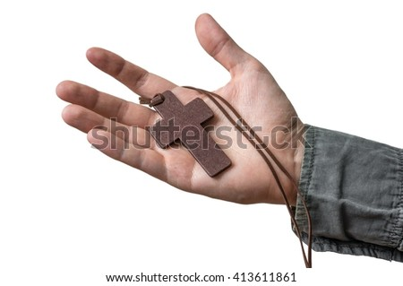 Hand of priest holds brown cross. Isolated on white background. - stock photo
