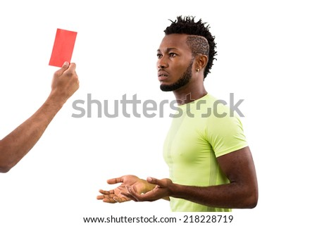 Hand of referee showing red card indicating dismissal for a match to the player - stock photo