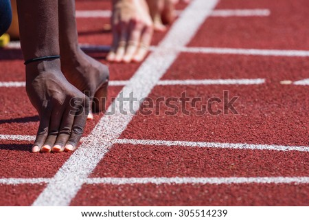 hand of runners on starting line in stadium - stock photo
