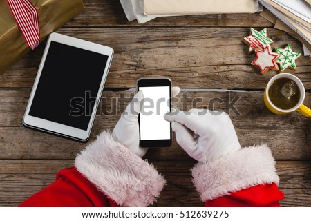 Hand of santa claus using mobile phone with christmas cookies and cup of coffee on wooden table