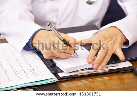 Hand of senior doctor taking notes in office - stock photo