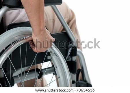 Hand of senior woman on wheelchair - stock photo
