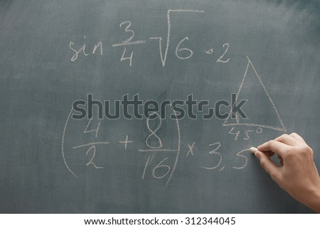 Hand of student studying mathematics and writing on a blackboard - stock photo