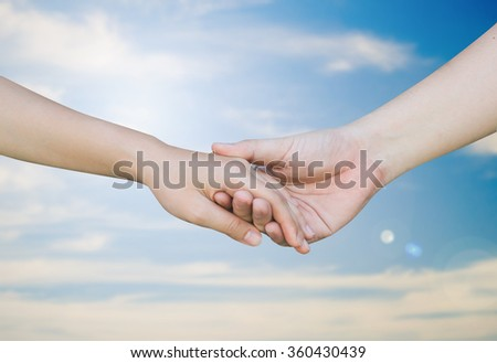 Hand of take care on blurred blue sky day background.
