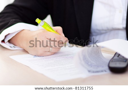 hand of the businesswoman writing note (hand with pen in focus) - stock photo