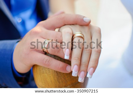 Hand of the groom and bride. The man holds the woman's hand. Wedding rings.