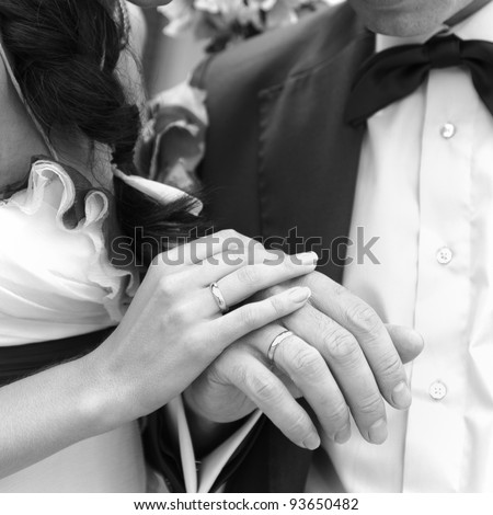 Hand of the groom and the bride with wedding rings. Monochrome image. - stock photo