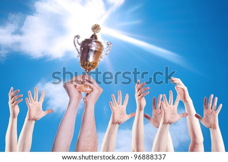 Hand of the person with a sports cup on a background of the bright sky. - stock photo