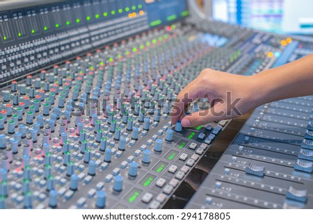 Hand of the professional audio musical mixer  - stock photo