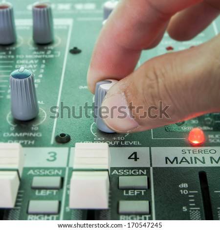 Hand of the sound producer and mixer console