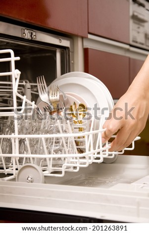 Hand of the woman taking out dishes from dishwasher