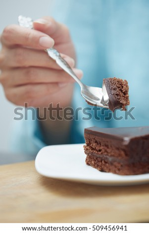 Hand of woman eating chocolate cake