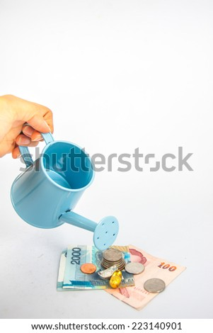 hand of woman hold blue watering can with money   (path in side) isolate on white ,Interpretive to money investment , glow up money - stock photo