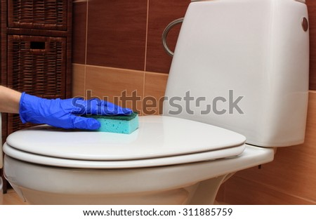 Hand of woman in blue glove cleaning toilet bowl, concept of house cleaning and household duties - stock photo