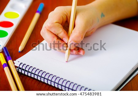 Hand of woman painter writing with color pencils into notebook, paint colors sitting beside on desk