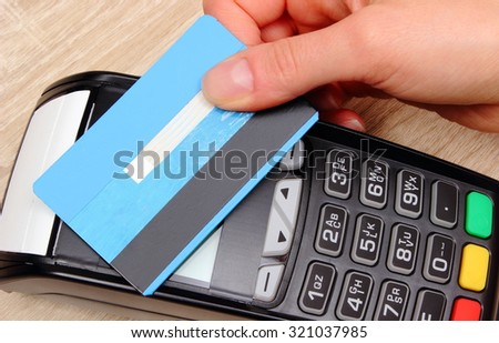 Hand of woman paying with contactless credit card with NFC technology, credit card reader, payment terminal, finance and banking concept - stock photo