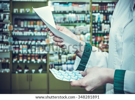 hand of woman pharmacist with prescription and pills at pharmacy. toned photo - stock photo