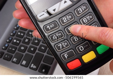 Hand of woman using payment terminal, enter personal identification number, credit card reader and laptop in background, finance and banking concept