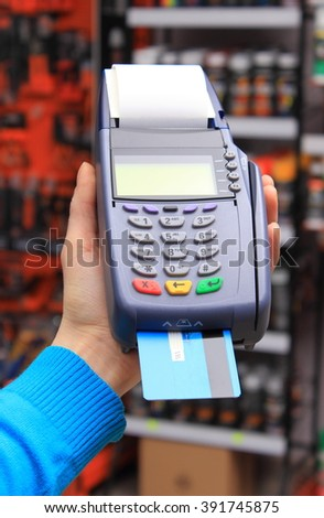 Hand of woman using payment terminal in an electrical shop, paying with credit card, credit card reader, finance concept - stock photo