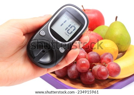 Hand of woman with glucometer and fresh natural fruits on cutting board in background, concept for healthy eating and diabetes