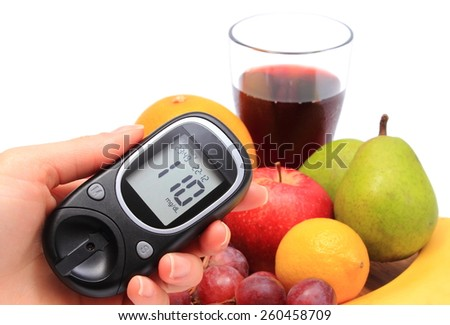 Hand of woman with glucose meter and fresh natural fruits on cutting board in background, concept for healthy eating and diabetes