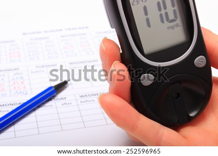 Hand of woman with glucose meter and medical form with results of measurement of sugar, concept for measuring sugar level - stock photo