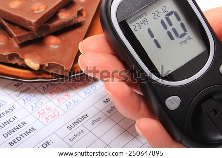 Hand of woman with glucose meter and portion of chocolate on medical form with results of measurement of sugar, concept of measuring sugar level - stock photo