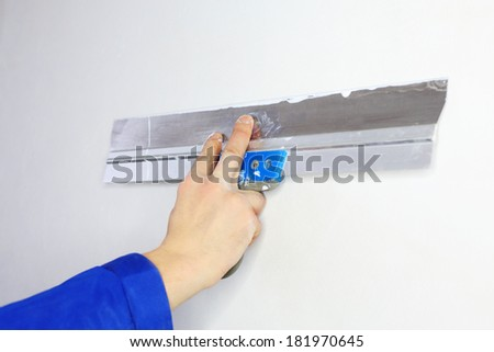 Hand of worker in blue clothes working by applicator in new apartment - stock photo