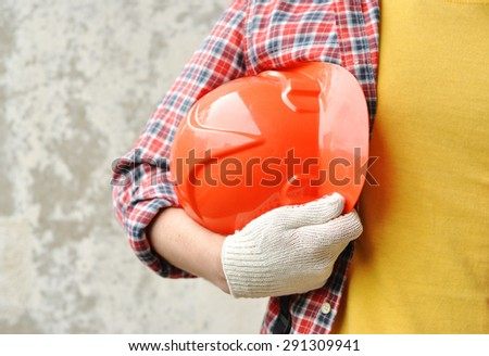 Hand of worker with red hard-hat