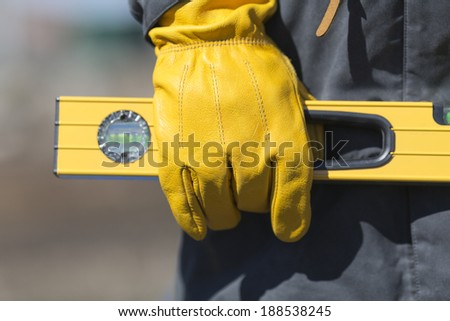 hand of worker with yellow glove and level - stock photo