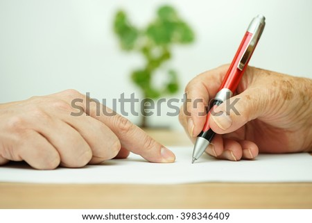 Hand of young adult pointing  elderly person where to sign - stock photo