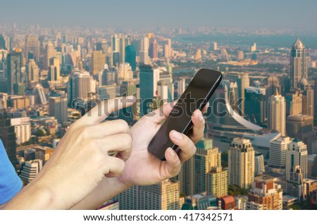 Hand of Young adult Tourist use Mobile Device smartphone over City Building Background - stock photo