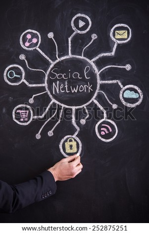 Hand of young man is drawing social network on blackboard.