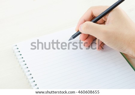 Hand of young man write on white notebook, hand write on notebook with black pencil