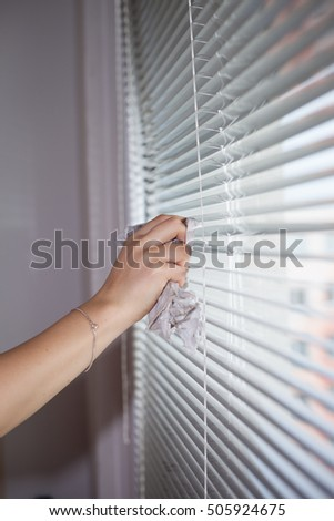 Hand of young woman cleaning blinds by cloth (vignette)