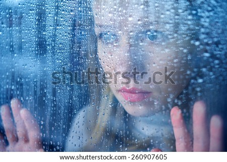 hand of young  woman  melancholy and sad  at the window in the rain - stock photo
